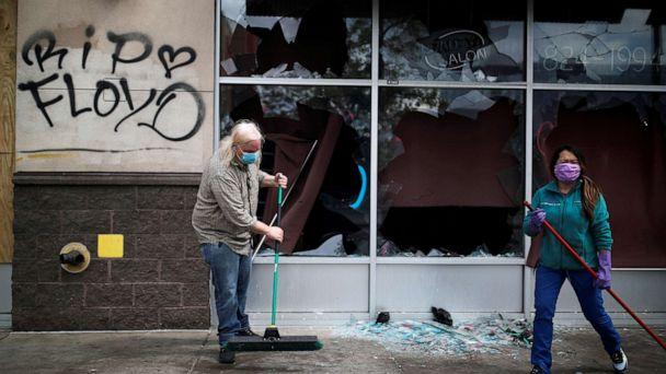 PHOTO: People clean up outside a local business in the aftermath of a protest after in Minneapolis, Minnesota, May 29, 2020. (Carlos Barria/Reuters)