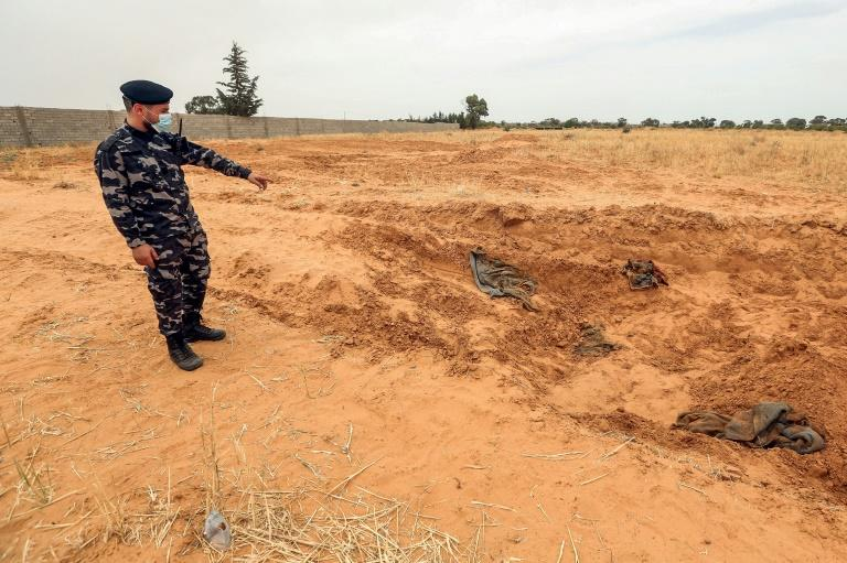A member of security forces affiliated with the GNA's Interior Ministry surveyed the reported site of a mass grave in the town of Tarhuna, southeast of the capital Tripoli