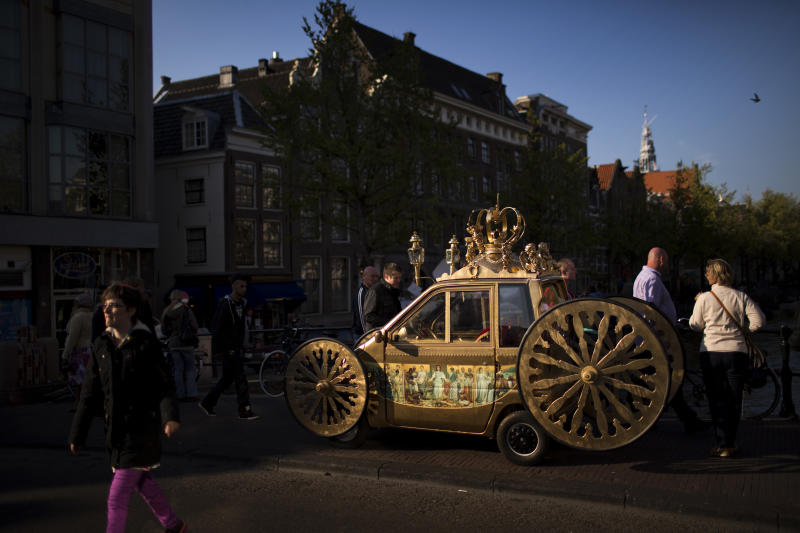 People walk past a car decorated as a royal carriage in downtown Amsterdam, Netherlands Sunday, April 28, 2013. Queen Beatrix announced she will relinquish the crown on April 30, 2013, after 33 years of reign, leaving the monarchy to her son Crown Prince Willem Alexander. (AP Photo/Emilio Morenatti)