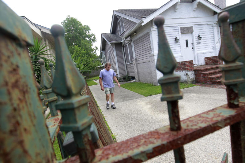 In this May 10, 2012 photo, homeowner Jim Provensal walks around a blighted home next door to his home, which is managed by the Louisiana Land Trust, an agency set up to handle the wrecked properties using federal funds, in New Orleans. More than 3,000 lots flooded by Hurricane Katrina and bought with federal money in an emergency bailout sit idle across this city: a multimillion-dollar drain on federal, state and city coffers that lends itself to no easy solution. An Associated Press examination of the properties sold to the government by homeowners abandoning New Orleans after the catastrophic 2005 flood has found that about $86 million has been spent on handling a total of 5,100 abandoned parcels. And there's no end in sight to maintenance costs for perhaps most of the 3,100 properties that remain unsold. (AP Photo/Gerald Herbert)