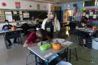 Marissa De Gaetano, center, looks over a student's shoulder as she teaches a class with students who are autistic during the coronavirus outbreak at Roosevelt High School - Early College Studies, Thursday, Oct. 15, 2020, in Yonkers, N.Y. (AP Photo/Mary Altaffer)