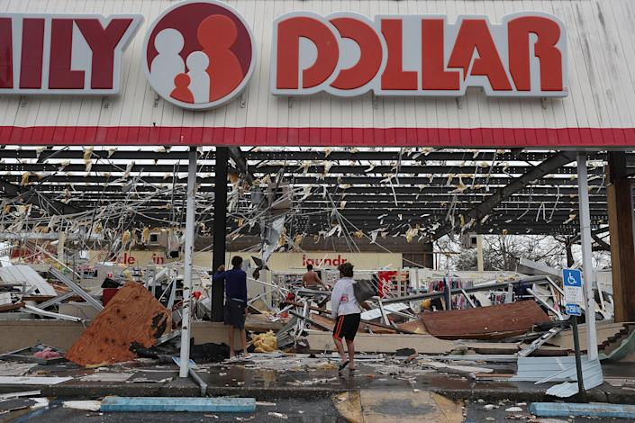 <p>People look on at a damaged store after Hurricane Michael passed through on Oct. 10, 2018 in Panama City, Fla. (Photo: Joe Raedle/Getty Images) </p>
