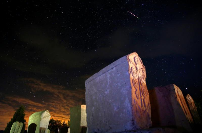 A meteor streaks past stars in the night sky above medieval tombstones in Radmilje near Stolac, south of Sarajevo, Bosnia and Herzegovina, August 12, 2016. — Reuters pic