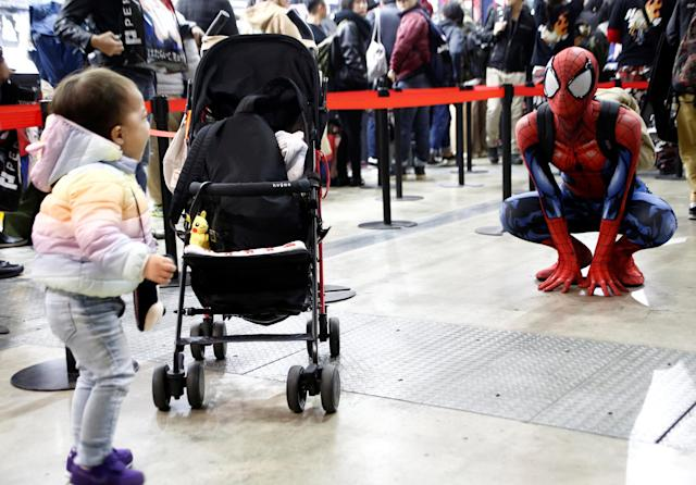 A baby boy cries as a man in a Spider-Man costume poses next to him at Tokyo Comic Con at Makuhari Messe in Chiba, Japan December 1, 2017. REUTERS/Kim Kyung-Hoon