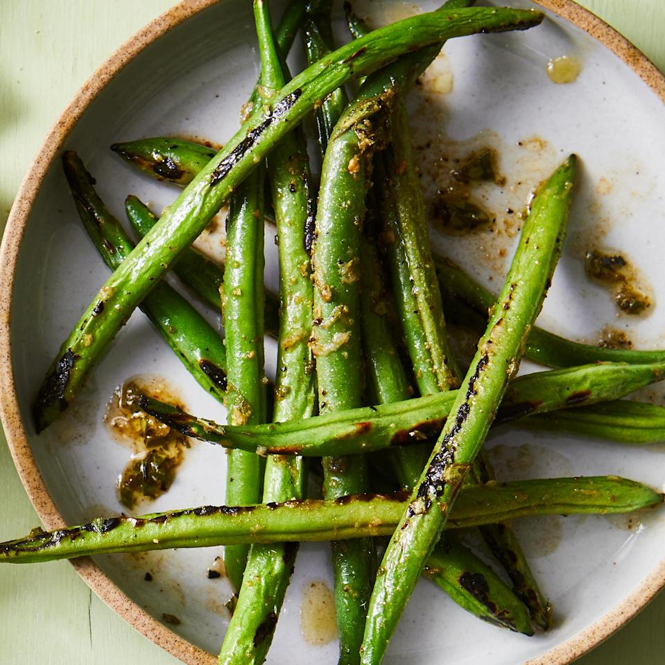 <p>Grilling green beans before tossing them in the marinade softens them up, helping them to absorb more of the flavor. Serve them as is or toss into a green salad.</p>