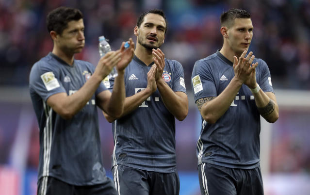 FILE - In this May 11, 2019 file photo, Bayern forward Robert Lewandowski, left, defender Mats Hummels, center and defender Niklas Suele greet supporters at the end of the German Bundesliga soccer match between Leipzig and Bayern Munich at the Red Bull Arena stadium in Leipzig. Fifty-four major titles compared to none, 119 years of existence against 10, some 290,000 club members versus 17 – the contrast between Bayern Munich and Leipzig could hardly be greater. The clubs meet in the German Cup final on Saturday, when Leipzig will bid for its first ever title and Bayern will hope to bring a happy end to a testing season with another domestic double. (AP Photo/Michael Probst)