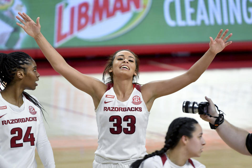 Arkansas guard Chelsea Dungee raises hands on the court.