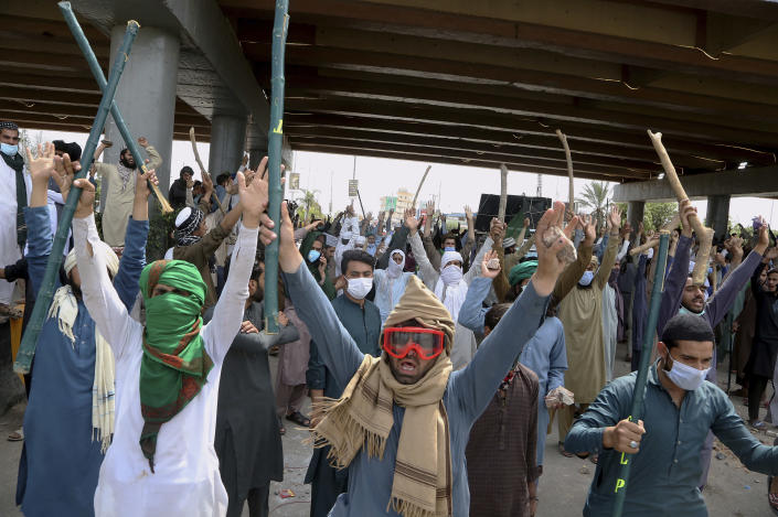Angry supporters of Tehreek-e-Labiak Pakistan, a radical Islamist political party, hold bamboo sticks and stones while shouting slogans at a protest against the arrest of their party leader Saad Rizvi, in Peshawar, Pakistan, Tuesday, April 13, 2021. Two demonstrators and a policeman were killed Tuesday in violent clashes between Islamists and police in Pakistan, hours after authorities arrested Rizvi in the eastern city of Lahore, a senior official and local media reported. (AP Photo/Muhammad Sajjad)