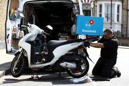 FILE PHOTO: A call out mechanic fixes a Dominos delivery scooter in the Clapham district of London