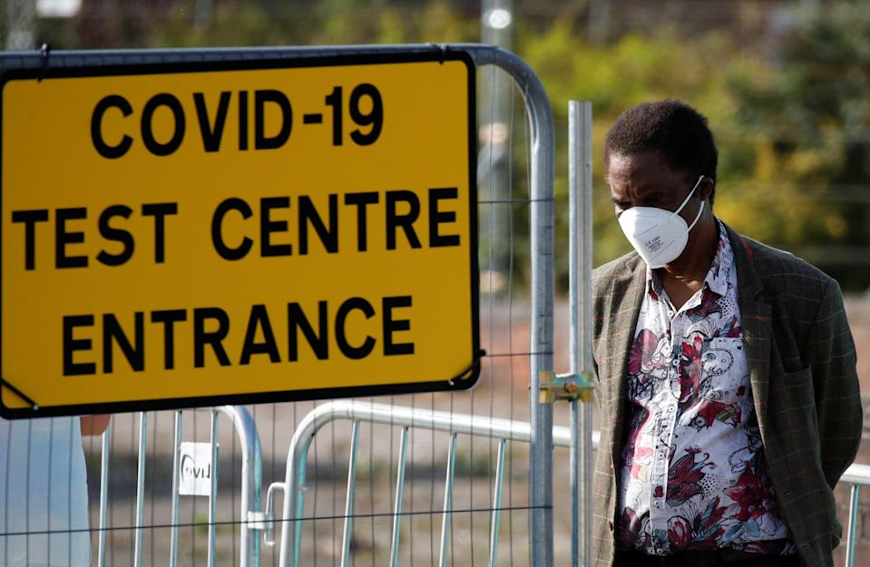 A man stands near a sign for a COVID-19 test centre in Bolton, Britain. Photo: Phil Noble/Reuters