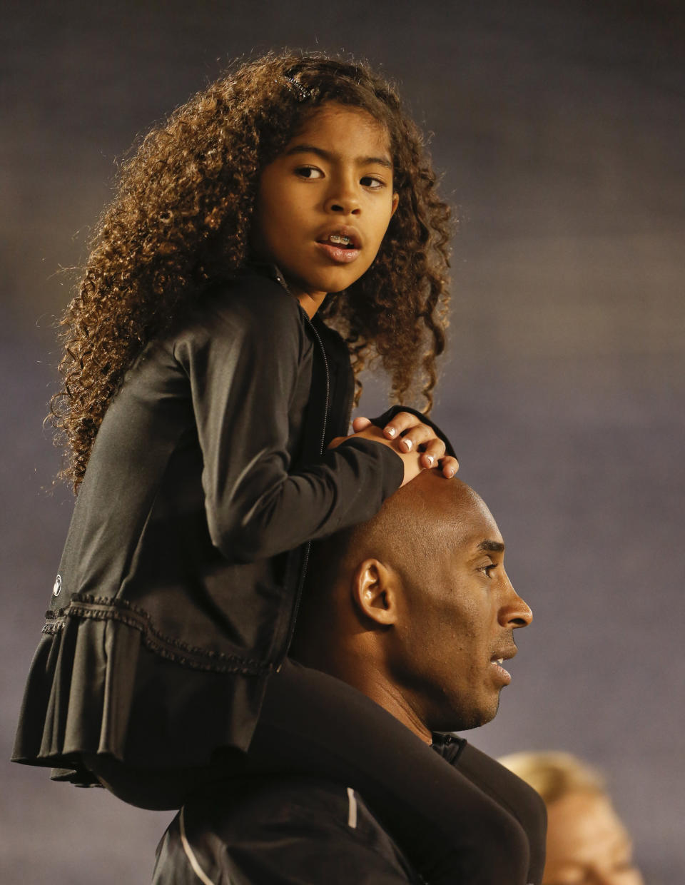 Gianna Maria-Onore Bryant sits on the shoulders of her father, Kobe, as they attend the women's soccer match between the United States and China Thursday, April 10, 2014, in San Diego. Bryant, the 18-time NBA All-Star who won five championships and became one of the greatest basketball players of his generation during a 20-year career with the Los Angeles Lakers, died in a helicopter crash Sunday, Jan. 26, 2020. Gianna also died in the crash. (AP Photo/Lenny Ignelzi, file)