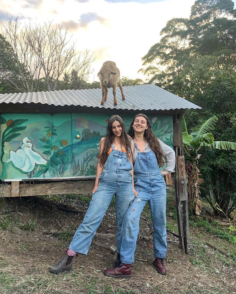 Julia and Anastasia stand in front of a hand painted shed and wear overalls. There is a sheep on top of the shed.