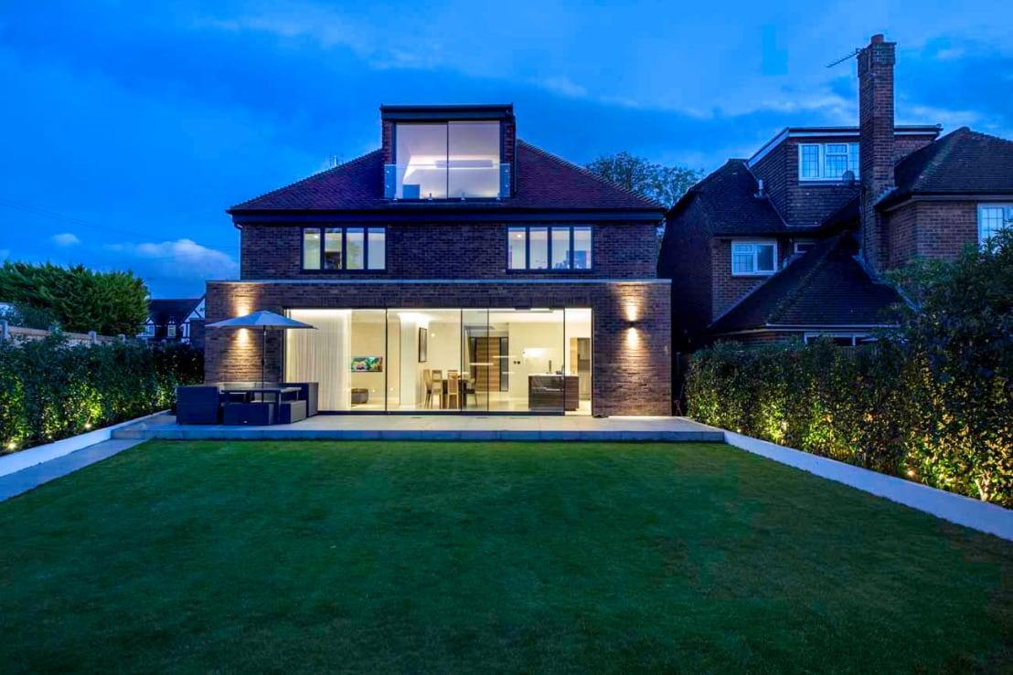 <p>At the rear, the house is decidedly more open (and modern), where more glazed surfaces make their presence known via generous windows and gigantic sliding doors.</p><p>And as if a stunning house wasn't enough, this location also gets to flaunt a striking (and most spacious) garden as well.</p>  Credits: homify / New Images Ltd