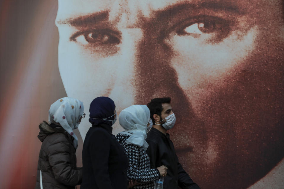 FILE - In this Tuesday, Nov. 17, 2020, file photo, people wearing masks to help protect from the spread of the coronavirus walk past a picture of Mustafa Kemala Ataturk, modern Turkey's founder in Istanbul. When Turkey changed the way it reports daily COVID-19 infections, it confirmed what medical groups and opposition parties have long suspected — that the country is faced with an alarming surge of cases that is fast exhausting the Turkish health system. The official daily COVID-19 deaths have also steadily risen to record numbers in a reversal of fortune for the country that had been praised for managing to keep fatalities low. With the new data, the country jumped from being one of the least-affected countries in Europe to one of the worst-hit.(AP Photo/Emrah Gurel, File)