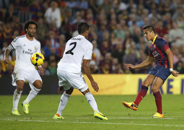 Barcelona's Alexis Sanchez, right, kicks the ball scoring a goal during a Spanish La Liga soccer match between Barcelona F.C. and Real Madrid at the Camp Nou stadium in Barcelona, Spain, Saturday, Oct. 26, 2013. (AP Photo/Emilio Morenatti)