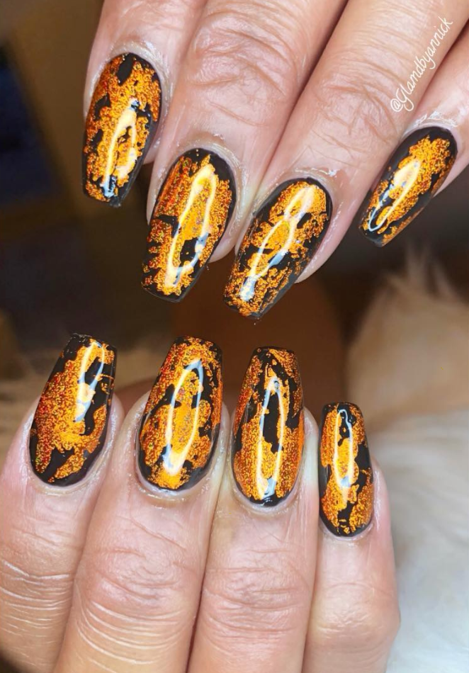 """<p>Get glammed up for a Halloween party with these shimmery metallic orange nails. Start with a black nail polish as the base, and after it dries, swirl the copper orange on top to recreate this gorgeous look <a href=""""https://www.instagram.com/glamdbyannick/"""" rel=""""nofollow noopener"""" target=""""_blank"""" data-ylk=""""slk:by nail artist Annick."""" class=""""link rapid-noclick-resp"""">by nail artist Annick.</a></p><p><a class=""""link rapid-noclick-resp"""" href=""""https://go.redirectingat.com?id=74968X1596630&url=https%3A%2F%2Fwww.etsy.com%2Flisting%2F247288838%2Fglory-red-orange-copper-gold-chartreuse%3Fref%3Dshop_home_active_26&sref=https%3A%2F%2Fwww.oprahmag.com%2Fbeauty%2Fskin-makeup%2Fg33239588%2Fhalloween-nail-ideas%2F"""" rel=""""nofollow noopener"""" target=""""_blank"""" data-ylk=""""slk:SHOP POLISH"""">SHOP POLISH</a></p>"""