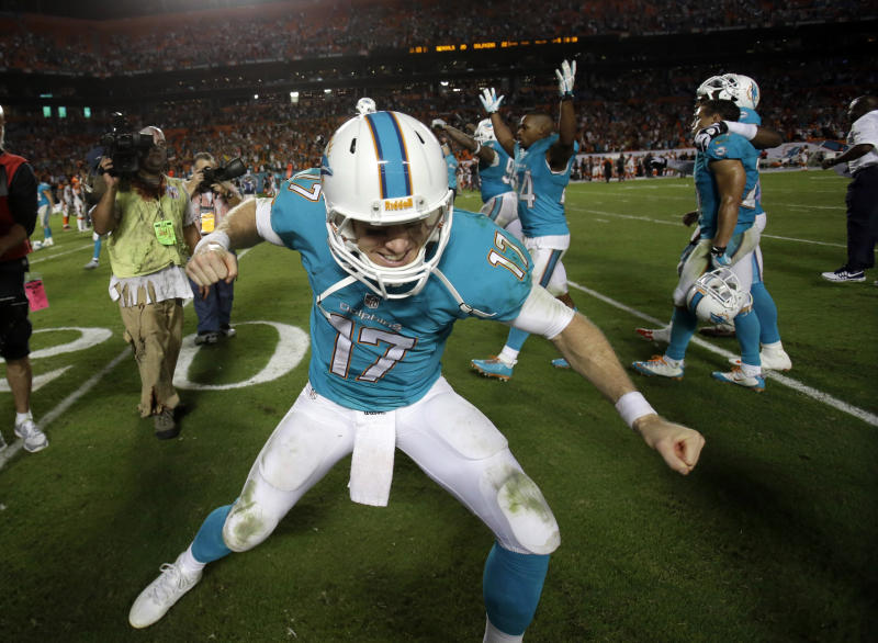 Miami Dolphins quarterback Ryan Tannehill (17) celebrates after the Dolphins defeated the Cincinnati Bengals 22-20 in overtime of an NFL football game on Friday, Nov. 1, 2013, in Miami Gardens, Fla. (AP Photo/Wilfredo Lee)