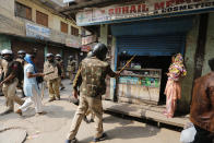 Indian security officers order a shop to be shut in New Delhi, India, Wednesday, Feb. 26, 2020. At least 20 people were killed in three days of clashes in New Delhi, with the death toll expected to rise as hospitals were overflowed with dozens of injured people, authorities said Wednesday. The clashes between Hindu mobs and Muslims protesting a contentious new citizenship law that fast-tracks naturalization for foreign-born religious minorities of all major faiths in South Asia except Islam escalated Tuesday. (AP Photo/Rajesh Kumar Singh)