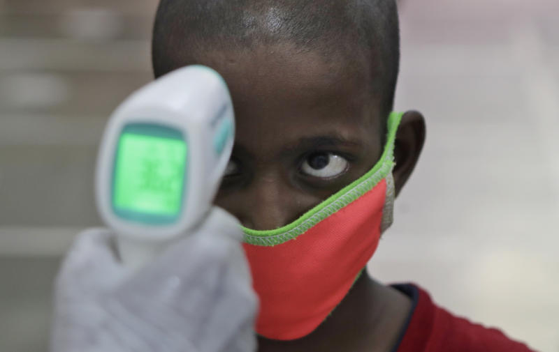 A health worker checks the body temperature of a boy at a medical camp to screen residents for COVID-19 symptoms in Mumbai, India, Friday, July 17, 2020. India crossed 1 million coronavirus cases on Friday, third only to the United States and Brazil, prompting concerns about its readiness to confront an inevitable surge that could overwhelm hospitals and test the country's feeble health care system. (AP Photo/Rajanish Kakade)