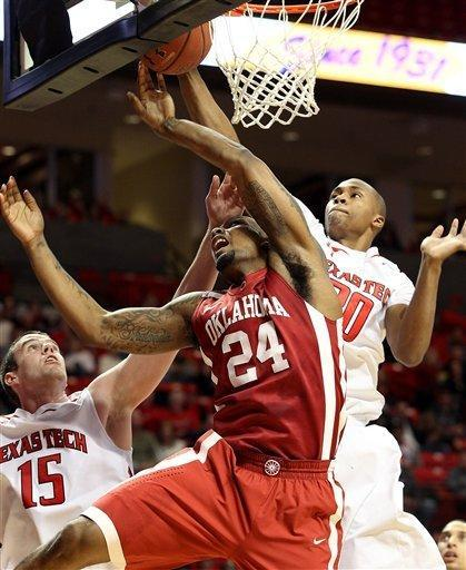 Oklahoma's Romero Osby (24) has his shot blocked by Texas Tech's Jaye Crockett (30) and Robert Lewandowski(15) during their NCAA college basketball game in Lubbock, Texas, Saturday, Feb. 11, 2012. (AP Photo/Lubbock Avalanche-Journal, Zach Long) ALL LOCAL TV OUT