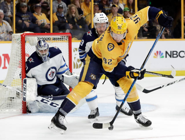 Nashville Predators center Ryan Johansen (92) passes the puck back between his skates in front of Winnipeg Jets defenseman Toby Enstrom (39), of Sweden, and goalie Connor Hellebuyck (37) during the second period in Game 1 of an NHL hockey second-round playoff series Friday, April 27, 2018, in Nashville, Tenn. (AP Photo/Mark Humphrey)