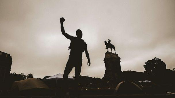 PHOTO: This photo taken on June 20, 2020, shows a silhouette of a man with his fist in the air at the Robert E. Lee monument in Richmond, Virginia. Protesters for racial justice have called for statues of Confederate leaders, like Lee, to be taken down. (Eze Amos/Getty Images)