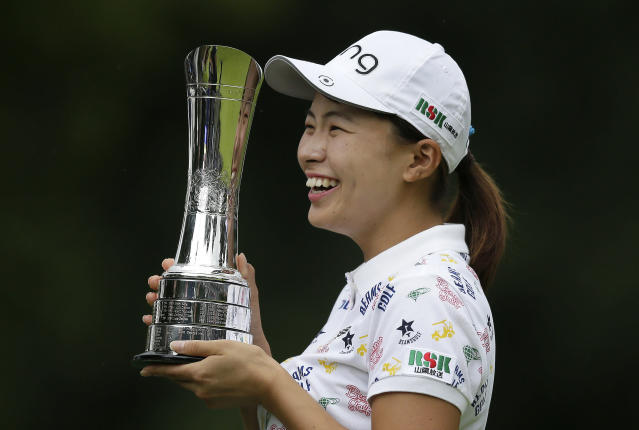 Japan's Hinako Shibuno smiles as he holds the trophy as she celebrates after winning the Women's British Open golf championship at Woburn Gold Club near near Milton Keynes, England, Sunday, Aug. 4, 2019. (AP Photo/Tim Ireland)