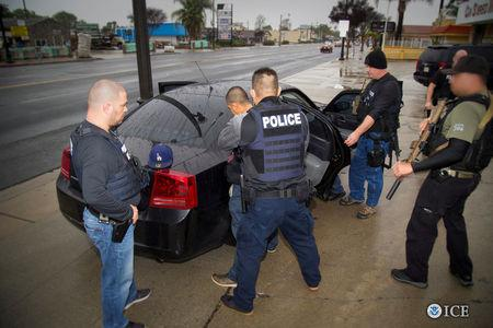 FILE PHOTO - ICE officers detain a suspect as they conduct a targeted enforcement operation in Los Angeles