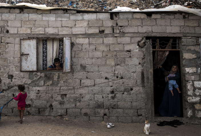 Palestinians are seen looking on from their house in a slum on the outskirts of Khan Younis Refugee Camp, in the southern Gaza Strip, Wednesday, Nov. 25, 2020. Israel's blockade of the Hamas-ruled Gaza Strip has cost the seaside territory as much as $16.7 billion in economic losses and caused its poverty and unemployment rates to skyrocket, a U.N. report said Wednesday, as it called on Israel to lift the 13-year closure. (AP Photo/Khalil Hamra)