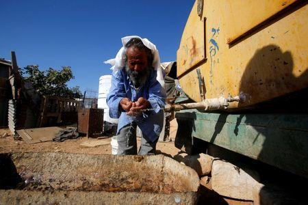 A Palestinian man washes his face from a water tank near his house on the outskirts of the West Bank village of Yatta, south of Hebron, August 17, 2016. REUTERS/Mussa Qawasma