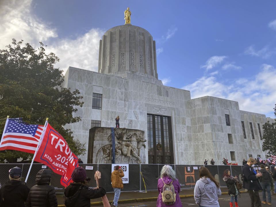 Protesters hold a rally outside the Oregon State Capitol in Salem, Ore. on Monday, Dec. 21, 2020, as legislators meet for a special session to discuss COVID-19 relief measures. State police declared an unlawful assembly at Oregon's Capitol building as protesters attempted to force their way in during the third special legislative session. (AP Photo/Sara Cline)