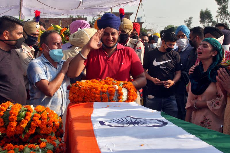 FILE PHOTO: Prabhjot Singh, son of Satnam Singh, an Indian soldier who was killed in a border clash with Chinese troops in Ladakh region, reacts next to the coffin of his father during his funeral ceremony in Bhojraj