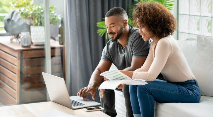 Young Black couple checks their dividends