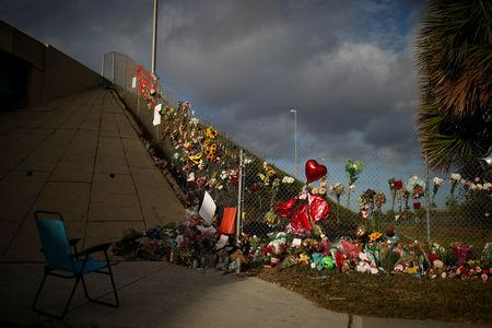 An empty chair is seen in front of flowers and mementoes placed on a fence to commemorate the victims of the mass shooting at Marjory Stoneman Douglas High School, in Parkland, Florida, U.S., February 20, 2018. REUTERS/Carlos Garcia Rawlins
