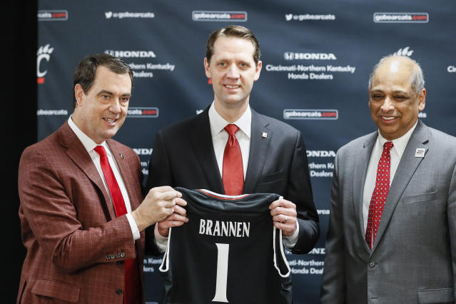 John Brannen, center, poses for a picture with athletic director Michael Robert Bohn, left, and university president Neville Pinto, right, during a news conference to formally announce Brannen's hiring as Cincinnati's men's basketball coach after leading Northern Kentucky to two NCAA Tournament appearances in the last three years, Monday, April 15, 2019, in Cincinnati. Brannen replaces Mick Cronin, who left Cincinnati for the UCLA job. (AP Photo/John Minchillo)