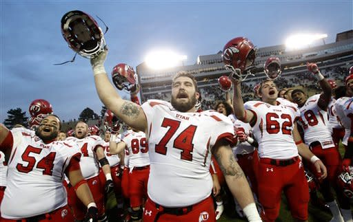 Utah players Tevita Stevens from left, Sam Brenner, Patrick Greene and Eric Rowe sing with fans after Utah's 42-35 victory over Colorado in an NCAA college football game in Boulder, Colo., on Friday, Nov. 23, 2012. (AP Photo/David Zalubowski)