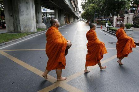 Buddhist monks cross a highway early morning in Bangkok, Thailand, in this September 9, 2015 file photo. REUTERS/Jorge Silva/Files
