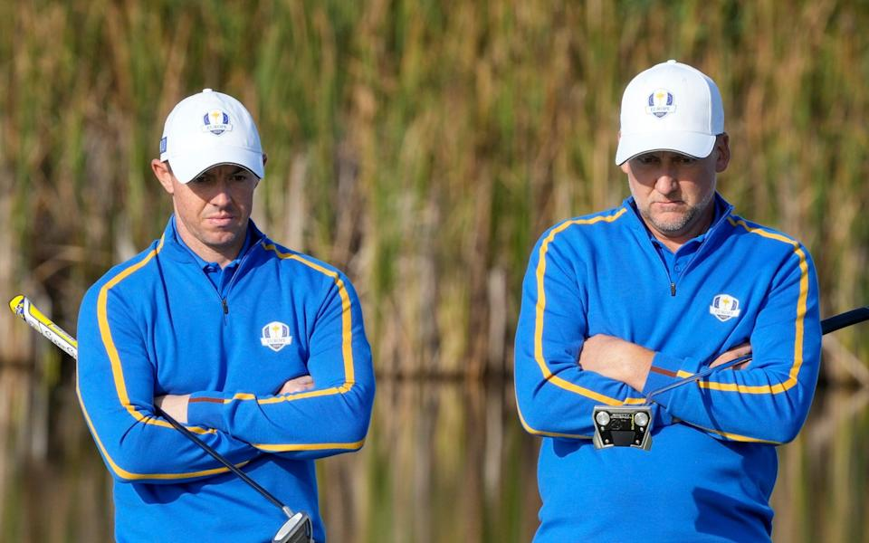 Rory McIlroy and Team Europe's Ian Poulter wait to putt on the fifth hole during a foursome match - AP