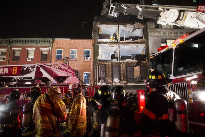 The facade of a four-story building on 14th Street and 8th Avenue collapsed onto the sidewalk as FDNY firefighters respond, Monday, Oct. 29, 2012, in New York. Hurricane Sandy bore down on the Eastern Seaboard's largest cities Monday, forcing the shutdown of mass transit, schools and financial markets, sending coastal residents fleeing, and threatening a dangerous mix of high winds, soaking rain and a surging wall of water up to 11 feet tall. (AP Photo/ John Minchillo)