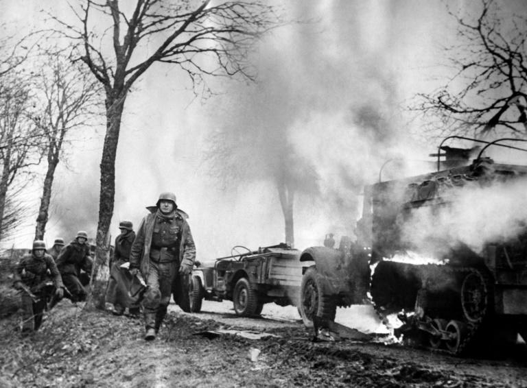 This photograph dated December 16, 1944, taken from a captured German's film, shows German infantrymen passing burning US Army vehicles somewhere on the Western Front