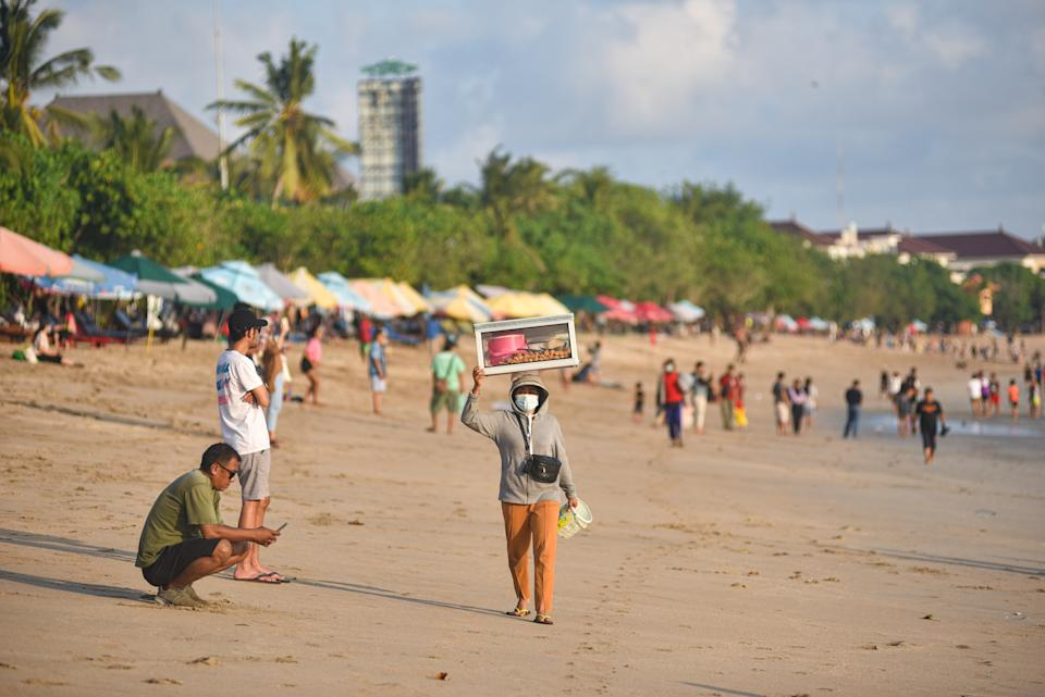 BADUNG, BALI, INDONESIA - 2021/06/14: A beach vendor carries her goods on her head at the beach. Bali as one of the world tourism destination closed its international tourism since Covid-19 outbreak in 2020 and now it prepares to reopen for tourists this July 2021. (Photo by Dicky Bisinglasi/SOPA Images/LightRocket via Getty Images)
