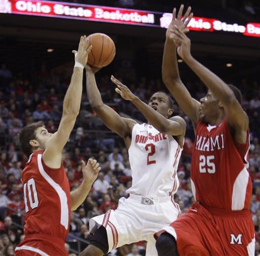 Ohio State's Jordan Sibert, center, drives to the basket against Miami (Ohio)'s Adam Thomas, left, and Jon Harris during the second half of an NCAA college basketball game Thursday, Dec. 22, 2011, in Columbus, Ohio. Ohio State won 69-40. (AP Photo/Jay LaPrete)