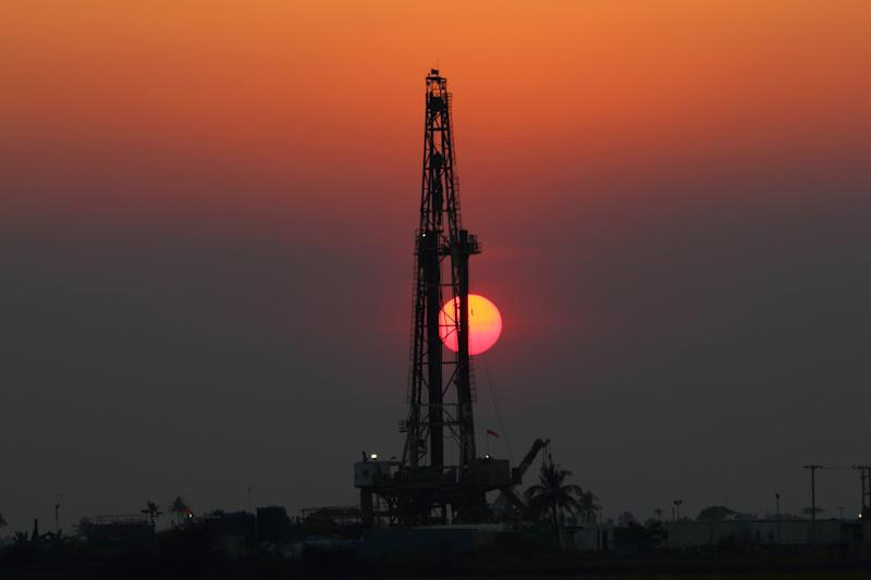 Drilling rig with the setting sun behind it.