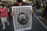 "A man holds a poster with an image of Peru's newly sworn-in President Manuel Merino with a message that reads in Spanish: ""He is not my president,"" during a protest by people who are refusing to recognize the new government, in Lima, Peru, Wednesday, Nov. 11, 2020. On Tuesday, Peru swore in Merino, the former congressional leader as president, after the legislature booted President Martin Vizcarra from office on Monday. (AP Photo/Rodrigo Abd)"