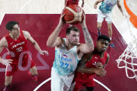 Slovenia's Luka Doncic (77) drives to the basket against Japan's Rui Hachimura, right, during a men's basketball game at the 2020 Summer Olympics, Thursday, July 29, 2021, in Saitama, Japan. (AP Photo/Eric Gay)