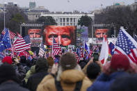 FILE - In this Jan. 6, 2021, file photo, the face of President Donald Trump appears on large screens as supporters participate in a rally in Washington. The House committee investigating the violent Jan. 6 Capitol insurrection, with its latest round of subpoenas in September 2021, may uncover the degree to which former President Donald Trump, his campaign and White House were involved in planning the rally that preceded the riot, which had been billed as a grassroots demonstration. (AP Photo/John Minchillo, File)