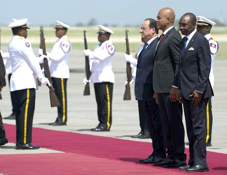 French President Francois Hollande(L) is received by the President of Haiti, Michel Martelly (C) and Prime Minister Evans Paul, in Port-au-Prince on May 12, 2015 (AFP Photo/Hector Retamal)