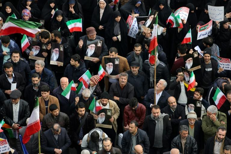 Iranian pro-government demonstrators raise national flags and pictures of the Islamic republic's supreme leader, Ayatollah Ali Khamenei (AFP Photo/ATTA KENARE)