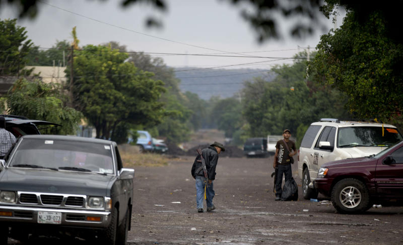 An armed man from the Self-Defense Council of Michoacan, (CAM), walks at a checkpoint set up by the self-defense group at the entrance to the town of Antunez, Mexico, Thursday, Jan. 16, 2014. Vigilantes in Michoacan state insist they won't lay down their guns until top leaders of a powerful drug cartel are arrested, defying government orders as federal forces try to regain control in a lawless region plagued by armed groups. (AP Photo/Eduardo Verdugo)