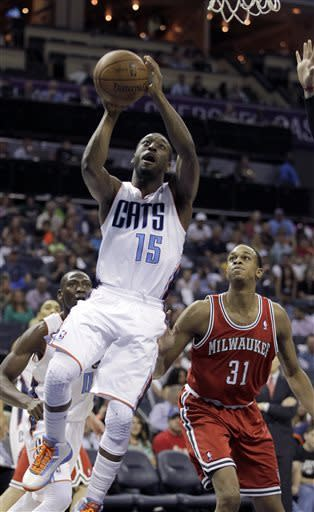 Charlotte Bobcats' Kemba Walker (15) gets by Milwaukee Bucks' John Henson (31) for a shot attempt during the first half of an NBA basketball game in Charlotte, N.C., Saturday, April 13, 2013. (AP Photo/Bob Leverone)
